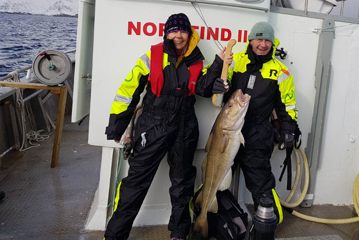 Man and woman holding cod on arctic cod fishing in Lofoten